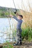 Stilig ung unge som rymmer hans metspö Royaltyfria Foton