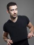 Stilig vänlig man som sträcker och visar mellanrum den svarta t-skjortan för annonsering royaltyfri bild