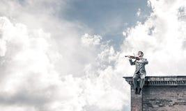 Stilig violinist i exponeringsglas på byggnadskantlek hans melodi Arkivfoto