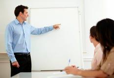 Stilig vuxen affärsman som pekar på whiteboarden royaltyfria bilder