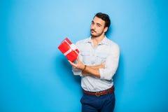 Stilig vuxen man på blå bakgrund med julgåvan arkivfoton
