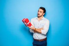 Stilig vuxen man på blå bakgrund med julgåvan fotografering för bildbyråer