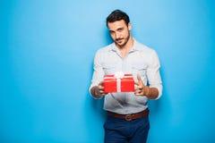 Stilig vuxen man på blå bakgrund med julgåvan royaltyfri foto