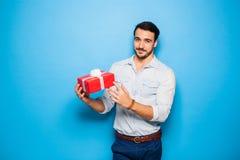 Stilig vuxen man på blå bakgrund med julgåvan arkivfoto