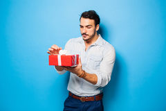 Stilig vuxen man på blå bakgrund med julgåvan arkivbilder