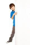 Lycklig pojke som ser från tom affischtavla Arkivfoton