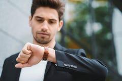 Stiliga affärsman- eller studentblickar på klockan Ung man i brådska sent för arbete Manlig modell på kontorsbyggnad royaltyfri bild