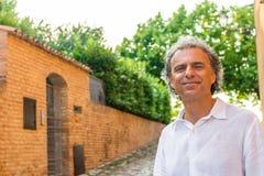 Stiliga gröna ögon kopplade av mannen nära medeltida väggar Fotografering för Bildbyråer