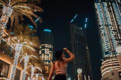 Stiliga kvinnor i trendig kläder för hatten, den brutala mannen, stilfull dräkt, går ner gatan kyla ljus och gömma i handflatan i fotografering för bildbyråer
