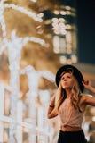 Stiliga kvinnor i trendig kläder för hatten, den brutala mannen, stilfull dräkt, går ner gatan kyla ljus och gömma i handflatan i arkivbilder