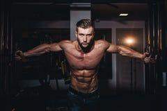 Stiliga män för muskulös kroppsbyggare som gör övningar i idrottshall med den nakna torson Stark idrotts- grabb med buk- muskler  Fotografering för Bildbyråer