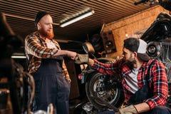 stiliga mekaniker som gör bronäven på motorcykeln fotografering för bildbyråer