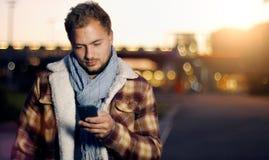 Stiliga sms för ung man som smsar genom att använda app på den smarta telefonen på autumen royaltyfri fotografi