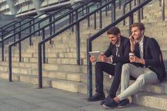 Stiliga unga affärsmän med grejen royaltyfria foton