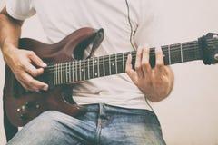 Stiliga unga asiatiska män som spelar gitarren och, lyssnar musik med H royaltyfri foto