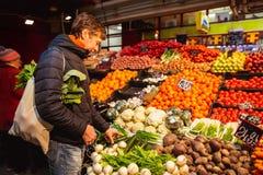 Stiliga unga män som rymmer ecoshoppingpåsen, medan stå i en matmarknad Man som väljer grönsaker royaltyfri bild