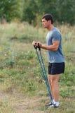 Stiliga unga muskulösa sportar man att öva yttersidan som är utomhus- med gummibandet Royaltyfri Foto