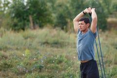 Stiliga unga muskulösa sportar man att öva yttersidan som är utomhus- med gummibandet Arkivbild