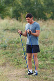 Stiliga unga muskulösa sportar man att öva yttersidan som är utomhus- med gummibandet Royaltyfria Bilder