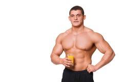 Stiliga unga muskulösa sportar man att rymma ett exponeringsglas av fruktsaft isolerat royaltyfria bilder