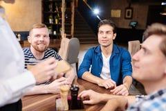 Stiliga vänner som talar till servitrins i bar arkivfoto