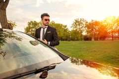 Stiligt affärsmananseende bredvid hans bil royaltyfri foto