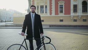 Stiligt affärsmananseende på en fyrkant nära cykeln stock video