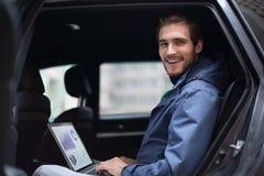 Stiligt affärsmansammanträde i den lyxiga limousineet som arbetar på bärbar datordatoren fotografering för bildbyråer