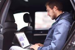 Stiligt affärsmansammanträde i den lyxiga limousineet som arbetar på bärbar datordatoren royaltyfri foto