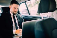 Stiligt affärsmansammanträde med bärbara datorn på backseaten av bilen arkivfoton