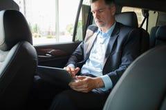 Stiligt affärsmansammanträde med bärbara datorn på backseaten av bilen royaltyfri fotografi