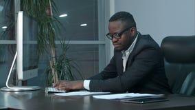 Stiligt afro--amerikan affärsmanarbete och maskinskrivning på bärbara datorn i kontoret lager videofilmer