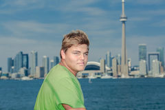 Stiligt anseende för tonårs- pojke mot blå bakgrund för sikt för Toronto stadssjö på solig varm dag arkivfoto