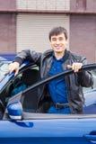 Stiligt anseende för ung man nära hans bil royaltyfri foto
