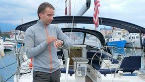 Stiligt anseende för ung man nära hans yacht Han kontrollerar meddelanden på den smarta klockan och möter vänner i ett socialt nä stock video