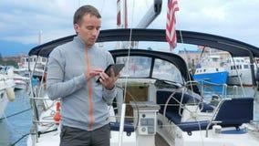 Stiligt anseende för ung man nära hans yacht Han kontrollerar meddelanden på minnestavlan och möter vänner i ett socialt nätverk stock video