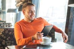 Stiligt arbete för ung man som ser in i minnestavlan, medan tycka om kaffe i kafé Royaltyfri Foto