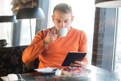 Stiligt arbete för ung man som ser in i minnestavlan, medan tycka om kaffe i kafé Royaltyfri Fotografi