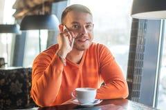 Stiligt arbete för ung man som talar på telefonen och ler, medan tycka om kaffe i kafé, blick på kameran Arkivfoton