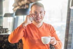 Stiligt arbete för ung man som talar på telefonen och ler, medan tycka om kaffe i kafé, blick på kameran Fotografering för Bildbyråer
