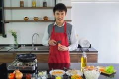 Stiligt Asain ung man som ler lycka för att förbereda mat i köket royaltyfria foton