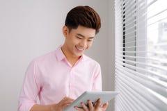 Stiligt asiatiskt mananseende med den digitala minnestavlan i regeringsställning royaltyfria foton