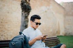 Stiligt asiatiskt manmaskinskrivningmeddelande på hans smarta telefonsammanträde på royaltyfri foto