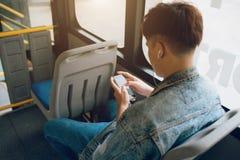 Stiligt asiatiskt mansammanträde i stadsbuss och överföringsmeddelande på th fotografering för bildbyråer
