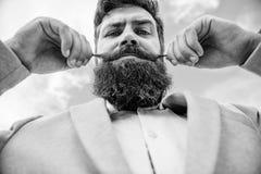 Stiligt attraktivt grabbslut för Hipster upp Expertspetsar för växande och underhållande mustasch Skäggig hipster för man fotografering för bildbyråer