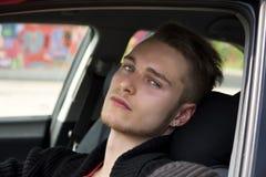 Stiligt blont sammanträde för ung man i hans bil royaltyfri bild