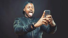 Stiligt bruk för ung man hans smarta telefon för ett selfieskott royaltyfri bild