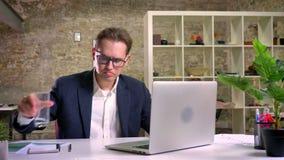 Stiligt caucasian affärsmansammanträde på tabellen och arbete bara på bärbara datorn i kontoret och dricksvattnet arkivfilmer
