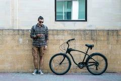 Stiligt cyklistanseende för ung man bredvid cykeln och hans seende Smartphone Stads- dagligt begrepp för gatalivsstil Arkivfoton