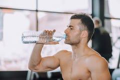Stiligt dricksvatten för ung man från en flaska i en idrottshall royaltyfri bild